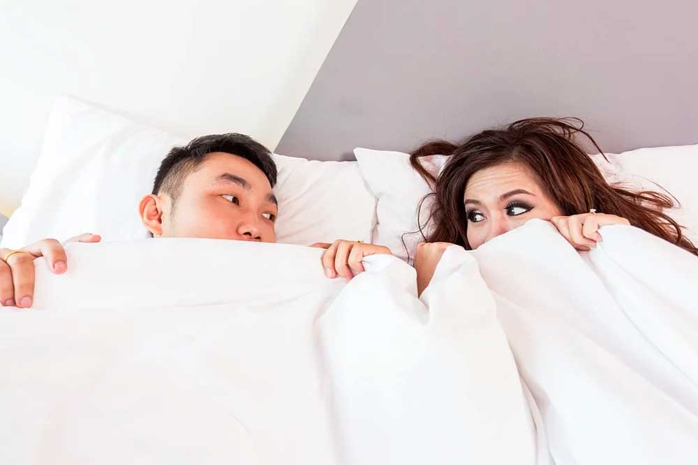 Young couple peeking out of the covers.